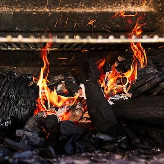 Płonące czerwone gorące iskry od płonącego węgla w grillu