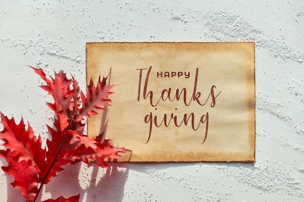 """Płonące czerwone liście dębu, długi cień. leżał na płasko, tekst """"happy thanksgiving"""" na starszej kartce papieru."""