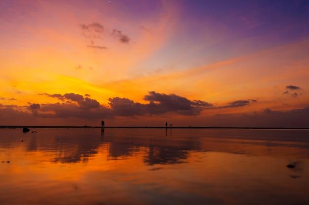 Płonące jasne niebo podczas zachodu słońca na tropikalnej plaży. zachód słońca podczas exodusu, siła ludzi chodzących po wodzie