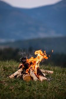 Płonące ognisko wieczorem w górach.