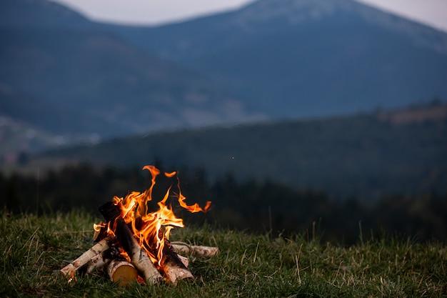 Płonące ognisko wieczorem w karpatach. miejsce na napis