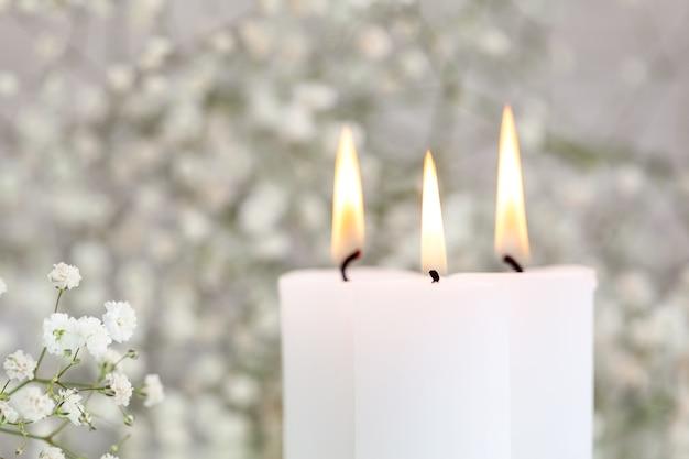 Płonące świece i gipsówki białe kwiaty na stole z miejscem na tekst. piękne pomysły na wystrój.
