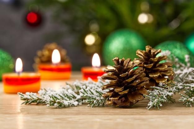 Płonące świece i ozdoby świąteczne. zielone kule na choinkę i gałązkę jodły
