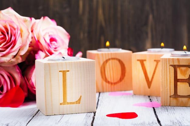 Płonące świece i słowo miłość wykonane z drewnianych świeczników