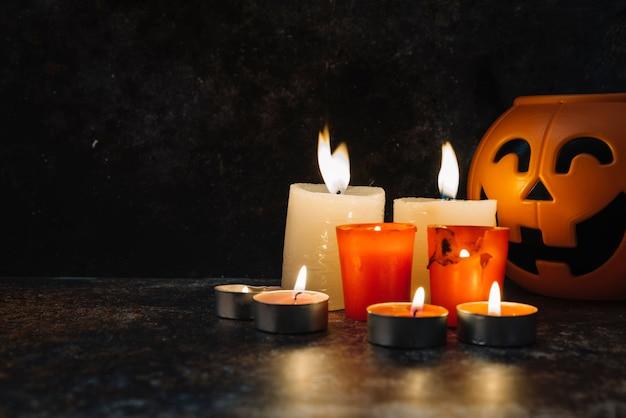 Płonące świece stały obok trick lub trick koszyka w stylu dyni