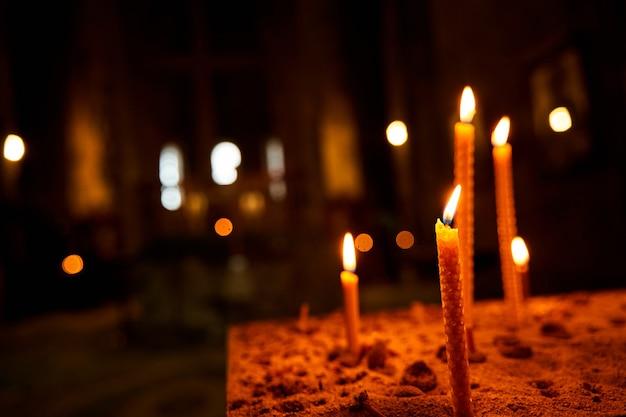 Płonące świece w kościele na ciemnym tle. świece pamięci. płonące świece w świątyni, święty ogień. świece płonące w ciemnym kościele.