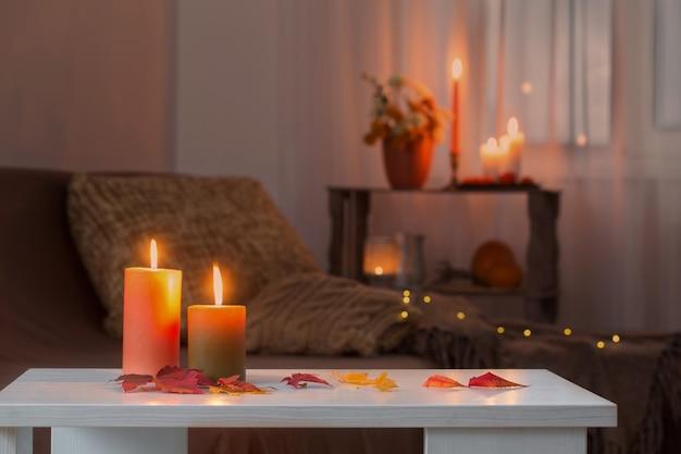 Płonące świece z jesiennym wystrojem na białym stole w domu