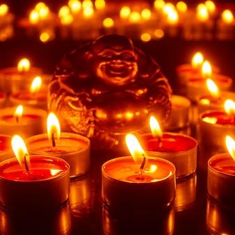 Płonące świeczki i figurka szczęśliwego buddy. skup się na przednich świecach