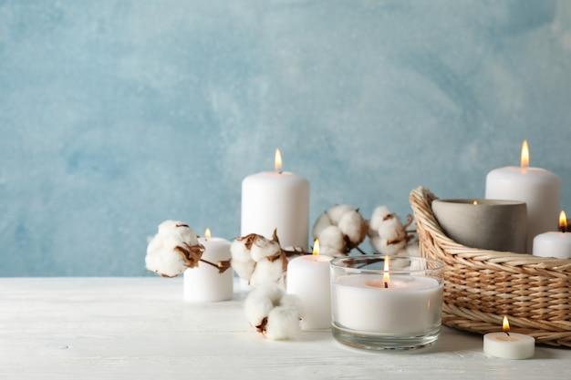 Płonące świeczki, kosz i bawełna na białym drewnianym stole