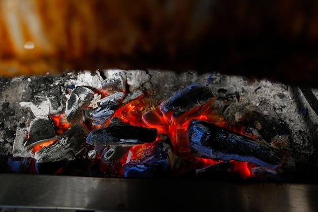 Płonące węgle drzewne pod widokiem z boku pieca do smażenia mięsa