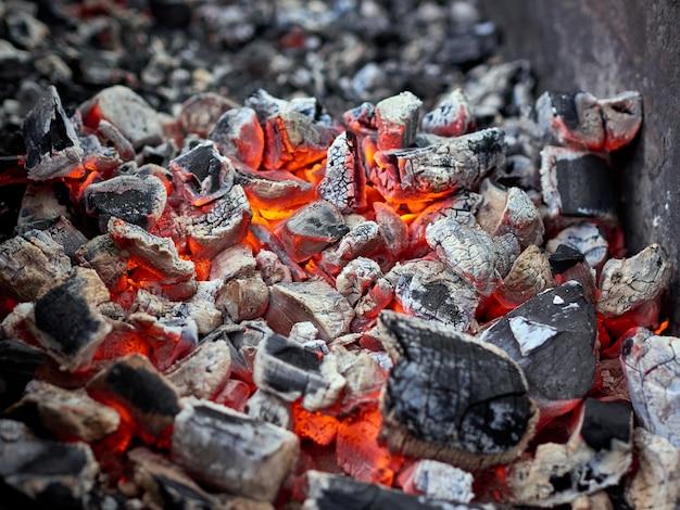 Płonący gorący węgiel drzewny w grillu grillowym