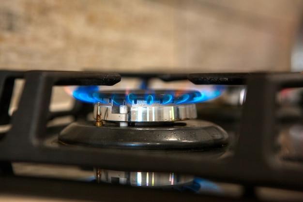 Płonący niebieski gaz na ciemnym piecu. kuchenka gazowa z palnikiem, koncepcja energii. zbliżenie, selektywna ostrość.