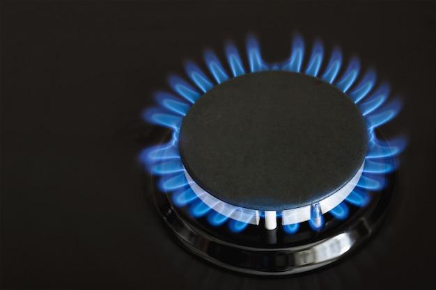 Płonący niebieski gaz na ciemnym piecu. palnikowa kuchenka gazowa, koncepcja energii.