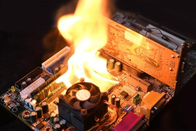Płonący ogień, płonąca płyta główna komputera, procesor, gpu i karta graficzna, procesor na płytce drukowanej z elektroniką