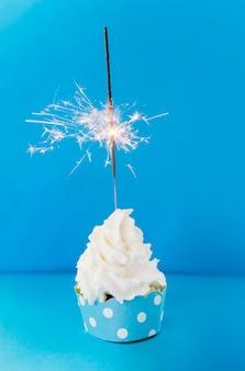 Płonący sparkler na śmietankowej babeczce przeciw błękitnemu tłu