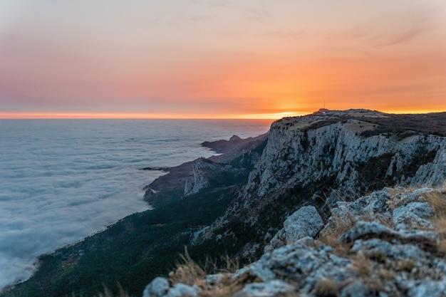 Płonący zachód słońca wysoko w górach, ponad chmurami.
