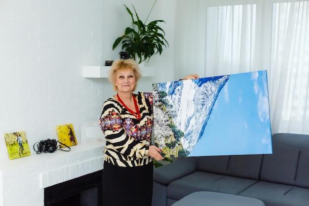 Płótno fotograficzne. blond starsza kobieta czuje się zmotywowana podczas robienia płótna fotograficznego