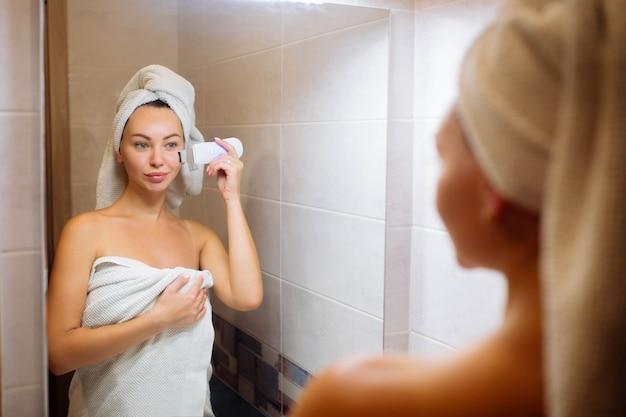 Płuczka ultradźwiękowa do oczyszczania skóry twarzy. dziewczyna w łazience dba o twarz.