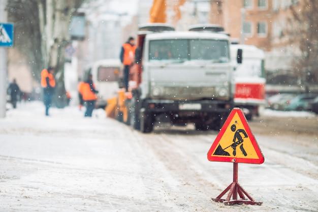 Pług odśnieżny usuwa śnieg z ulicy miasta. znak drogowy ostrzegawczy. praca pojazdu odśnieżającego odśnieżarki. czyszczenie zaśnieżonych zamarzniętych dróg.