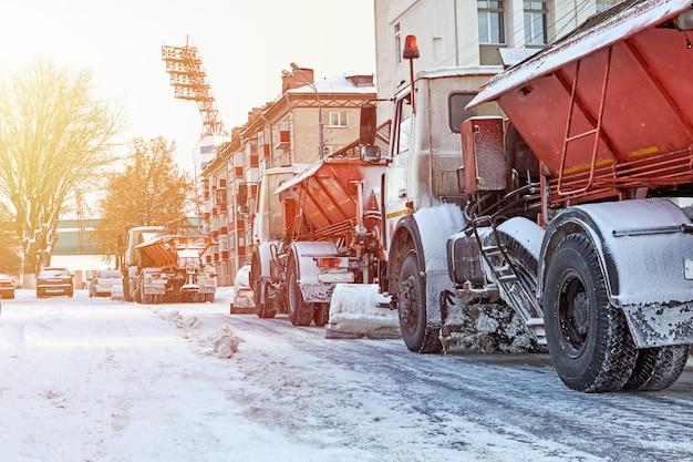 Pług śnieżny odśnieżający z drogi miejskiej. ciężarówka pług śnieżny pracuje na ulicy