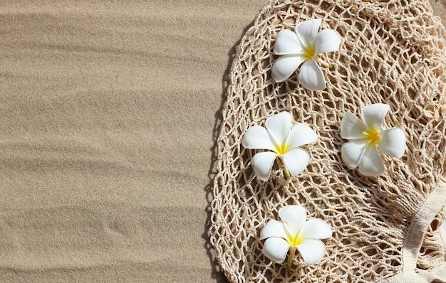 Plumeria kwiaty na siateczkowej torbie plażowej na piasku.