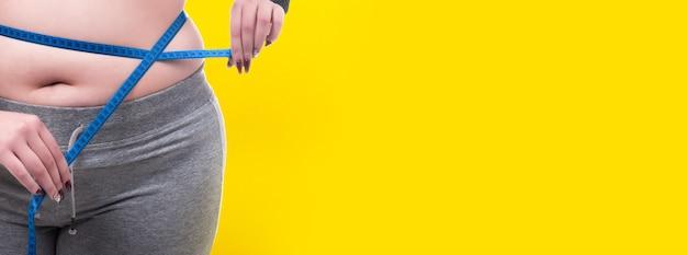 Plus rozmiar kobieta mierzy talię na żółtej ścianie, pojęcie otyłości