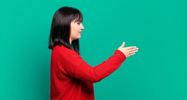 Plus rozmiar ładna kobieta uśmiecha się, wita cię i oferuje uścisk dłoni, aby zamknąć udaną transakcję, koncepcja współpracy