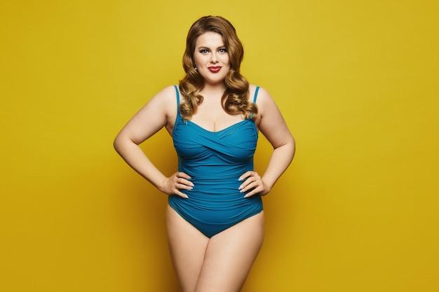 Plus rozmiar model dziewczyna ze stylową fryzurą i czerwonymi ustami w modny strój kąpielowy na żółtym tle, na białym tle.