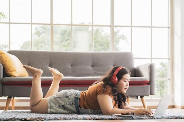 Plus size kobieta w słuchawkach z notebooka komputerowego leżącego na dywanie, czytając książkę i pracując w domu