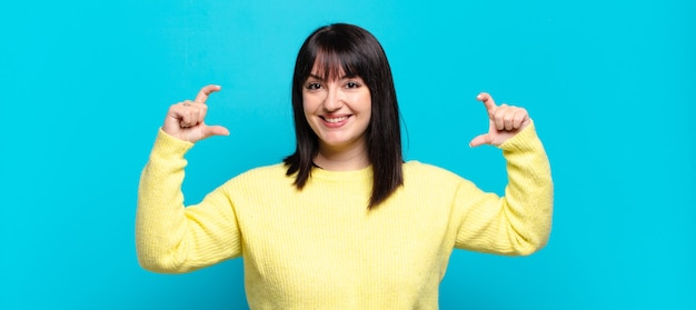 Plus size ładna kobieta oprawiająca lub zarysowująca swój uśmiech obiema rękami, wyglądająca pozytywnie i szczęśliwie, koncepcja wellness