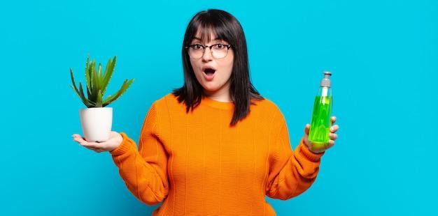 Plus size ładna kobieta trzyma kaktusa. koncepcja aloesu