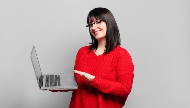 Plus size ładna kobieta uśmiecha się radośnie, czuje się szczęśliwa i pokazuje koncepcję w przestrzeni kopii z dłonią