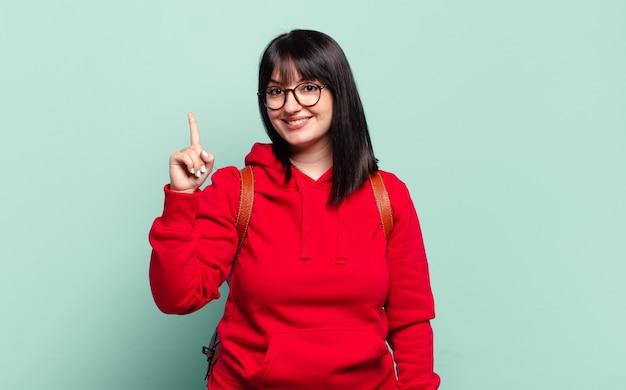Plus size ładna kobieta uśmiechnięta i wyglądająca przyjaźnie, pokazująca numer jeden lub pierwsza z ręką do przodu, odliczająca w dół