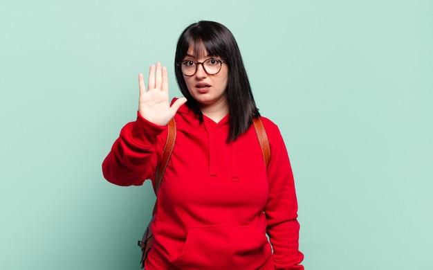 Plus size, ładna kobieta wyglądająca poważnie, surowo, niezadowolona i zła, pokazująca otwartą dłoń wykonującą gest stop
