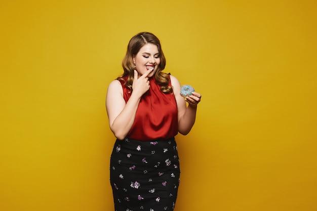 Plus size model kobieta w czerwonej satynowej bluzce i czarnej spódnicy gotowa zjeść smacznego pączka, na białym tle