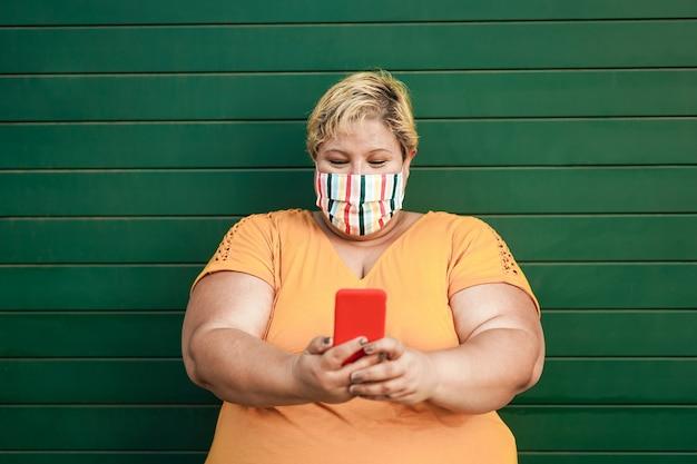Plus size szczęśliwa kobieta za pomocą smartfona nosząc maskę ochronną - skup się na twarzy