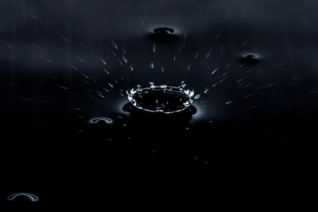 Plusk kropli wody na czarnym tle