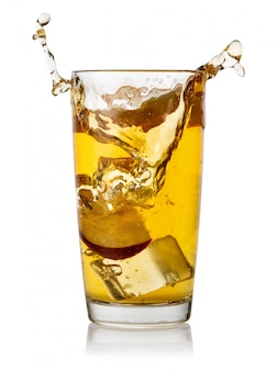 Plusk lodu i plasterki jabłka w szklance soku jabłkowego