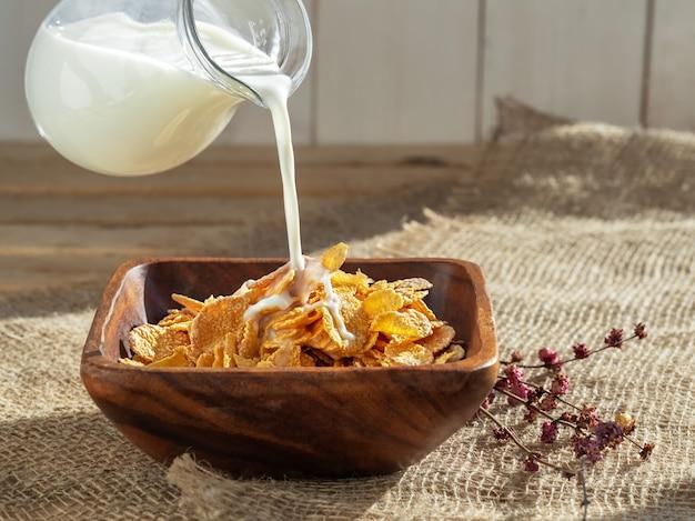 Plusk mleka na drewnianej misce z płatków kukurydzianych zbóż