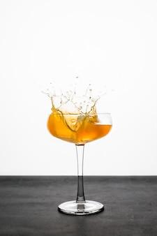Plusk pomarańczowego koktajlu w szkle coupe