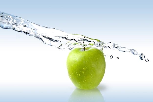 Plusk świeżej wody na zielone jabłko na białym tle