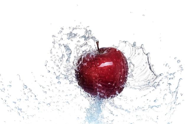 Plusk wody na czerwonym jabłku. na białym tle.