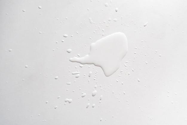 Plusk wody podświetlony na białej powierzchni stołu, abstrakcyjne krople deszczu