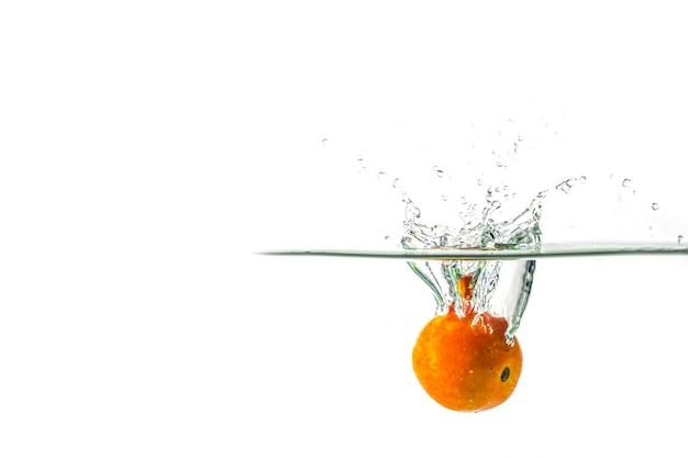 Plusk wody pomidorowej na białym tle