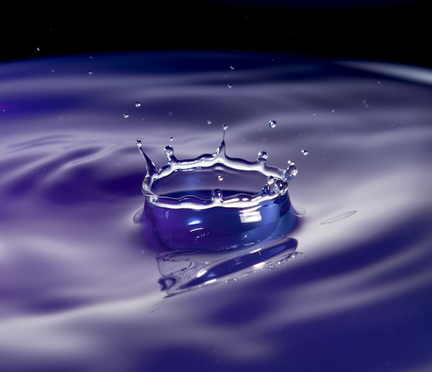 Plusk wody w fioletowym odcieniu z czarnym tłem