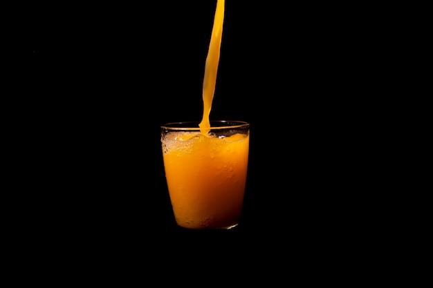 Pluśnięcie sok pomarańczowy na czarnym tle