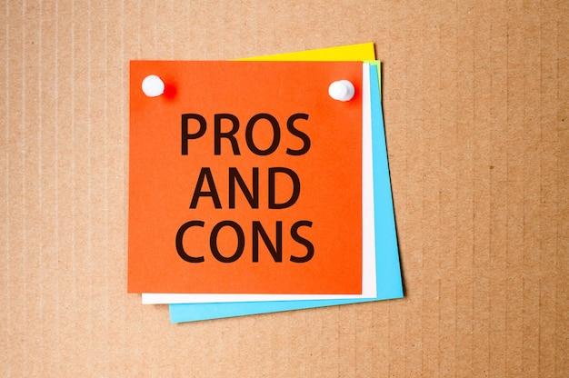 Plusy i minusy napisane na czerwonym papierze i przypięte na tablicy korkowej
