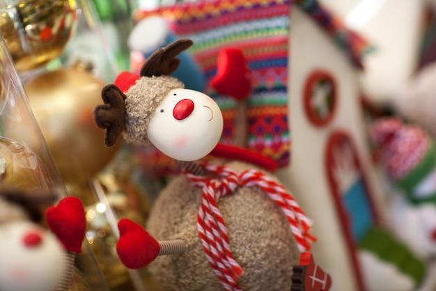 Pluszak świąteczny jeleń z szalikiem na tle domu