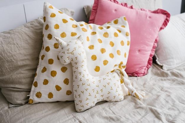 Pluszowa zabawka jednorożec biała ze złotem spoczywająca na poduszce w sypialni dziecka