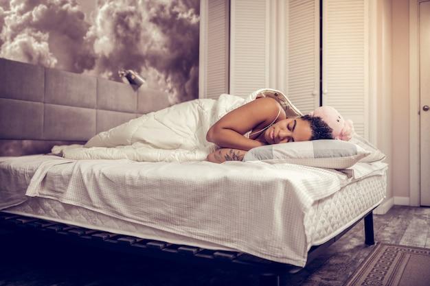 Pluszowa zabawka w pobliżu. afroamerykanka pokryta tatuażami, leżąca na szerokim łóżku i dobrze spana
